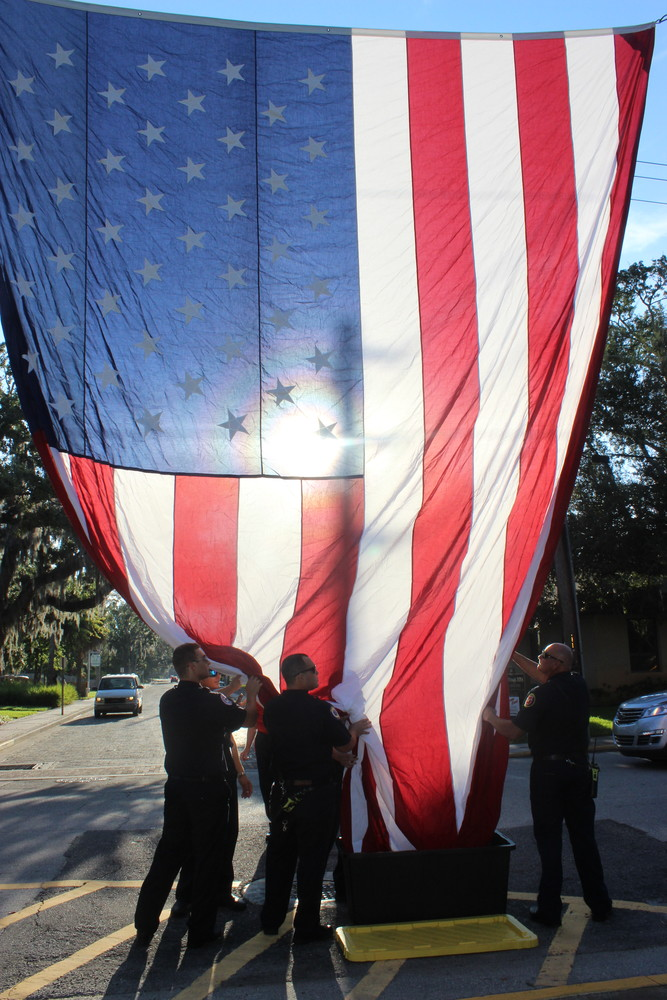 Local firefighters raise the American flag prior to the ceremony.