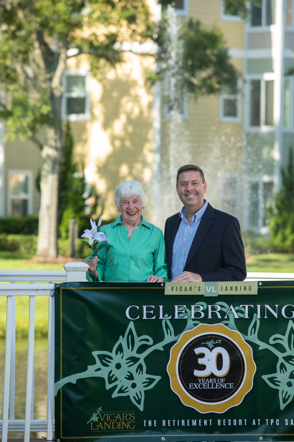 Longtime Vicar's Landing resident Cynthia Prince and Vicar's Landing CEO Bruce Jones stand in front of a banner celebrating the retirement community's 30th anniversary.