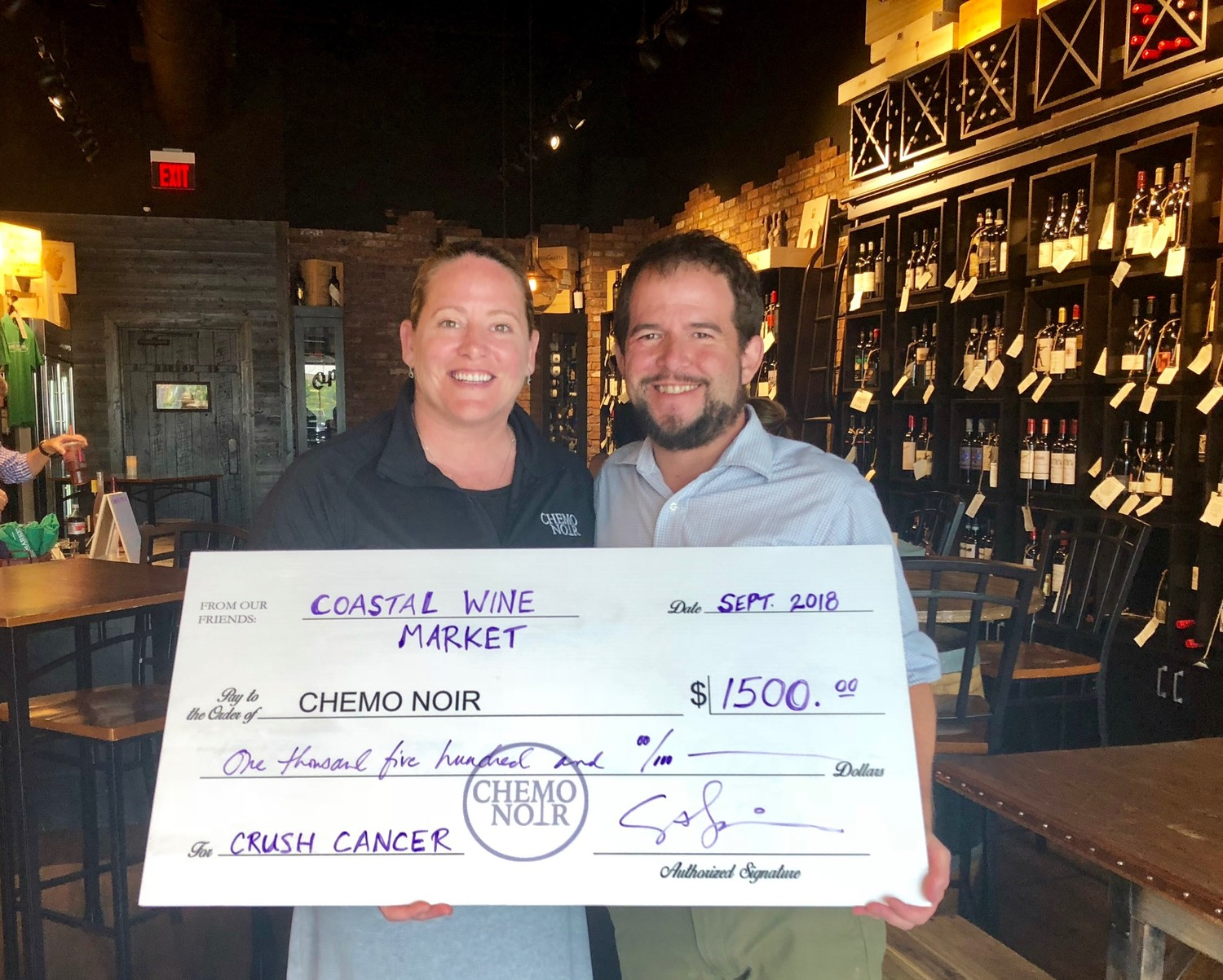 Katrin Casey, the founder of local nonprofit Chemo Noir, receives a check donation from Steven Lourie, co-owner of Coastal Wine Market & Tasting Room, for $1,500. The nonprofit, which provides financial support for cancer patients undergoing treatment, raised the funds at a recent CRUSH Cancer event held at the local wine shop.