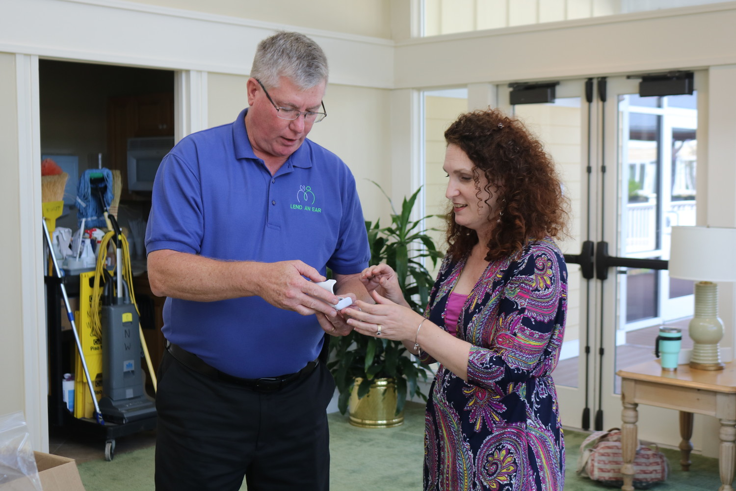 Lend an Ear Outreach Executive Director Scott Hetzinger presents a pair of hearing aids to Sonia Howley of the St. Johns County School District on Friday, Sept. 28 at Vicar's Landing.
