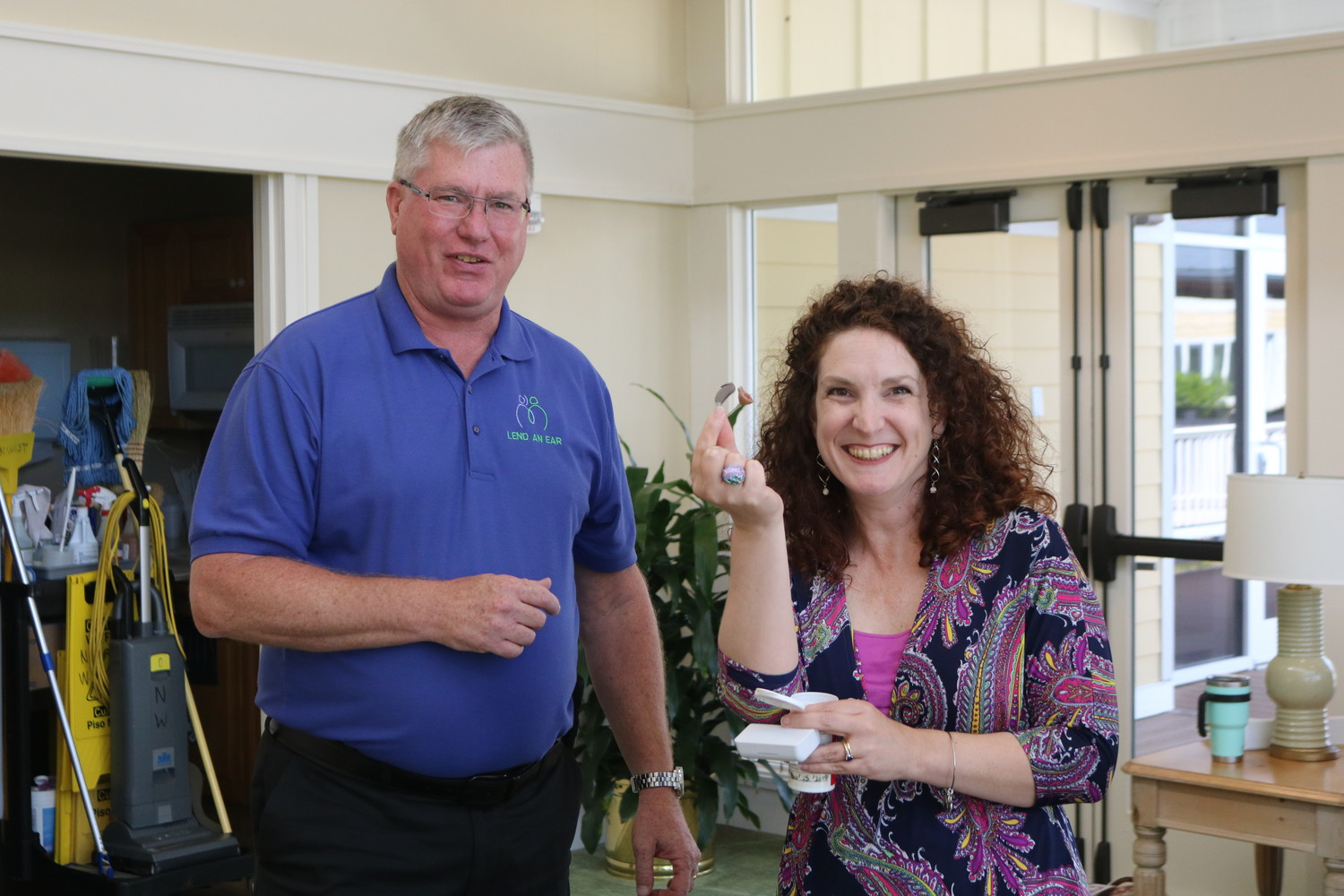 Sonia Howley of the St. Johns County School District celebrates as she receives the donated hearing aids from Lend an Ear Outreach Executive Director Scott Hetzinger.