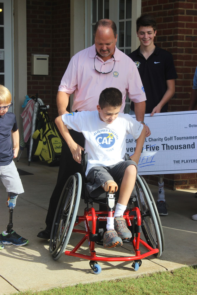 Jim Houston helps Daniel into his new wheelchair, which was presented to him as a surprise gift.