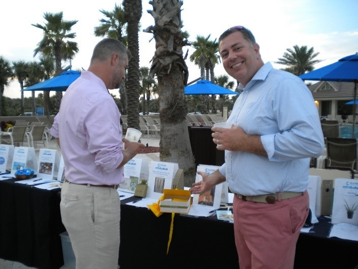 Blue Wavers review silent auction items at the Blue Wave Coalition Beach Bash