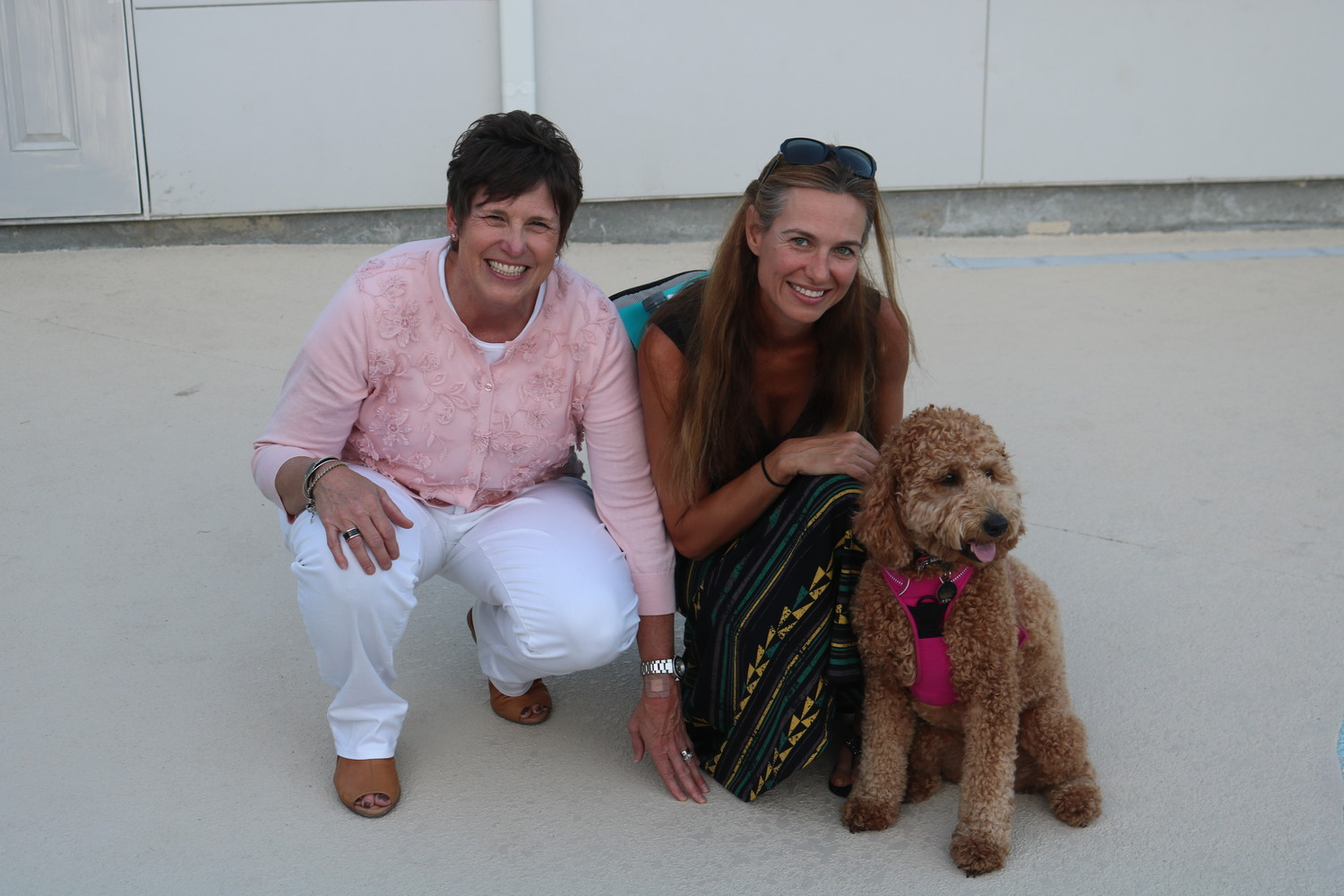 Dina Beam, the vice president of operations for Pet Paradise, poses for a photo with Kim Albers and her dog Ray at the Sept. 25 VIP party celebrating the opening of the business' Bartram location.