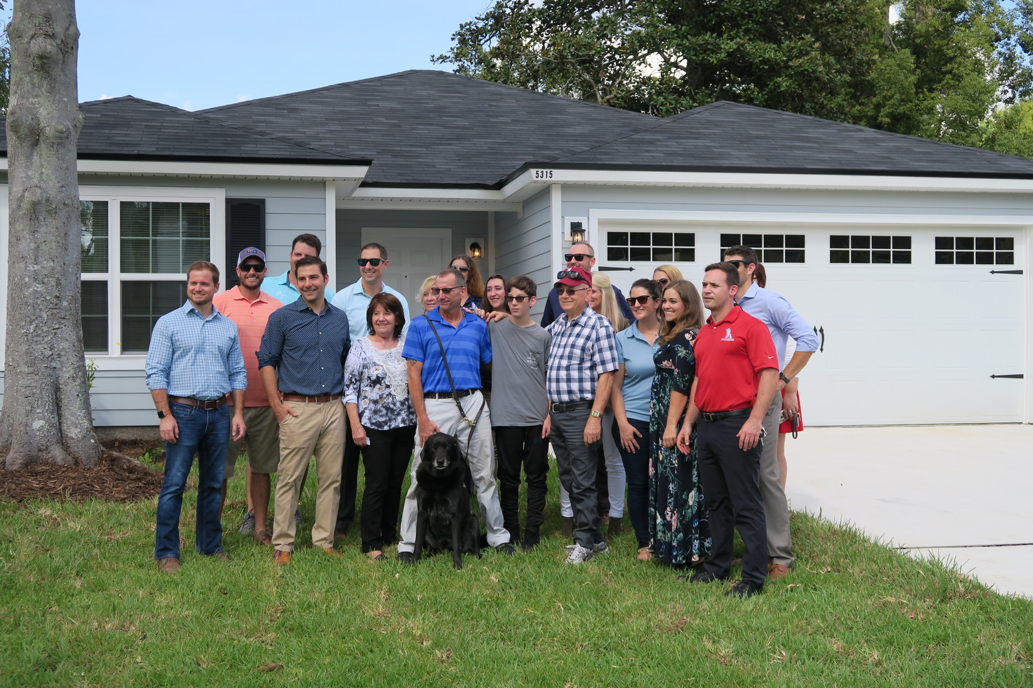 JWB Real Estate and K9s For Warriors staff pose with Smith and Berkley in front of their new home.