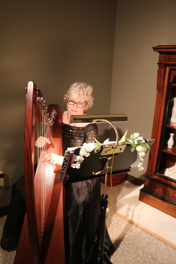 Harpist Andrea Akers entertains guests with live music.