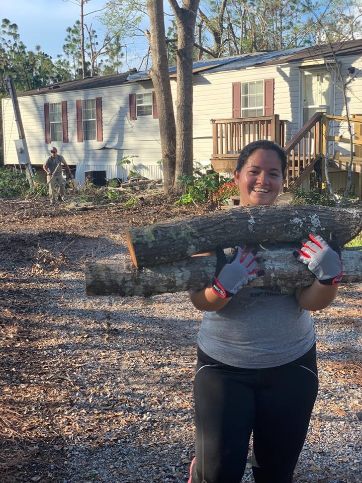 Jesica Martinez clears logs and brush from a home in Panama City.