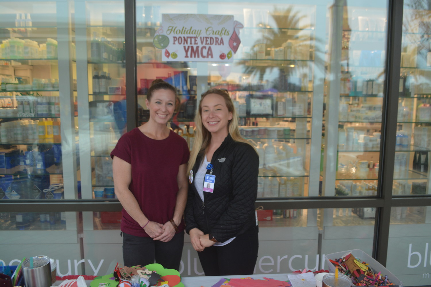 Erin Dankworth and Becky Richmond of the Ponte Vedra YMCA pose for a photo behind their holiday crafts table.
