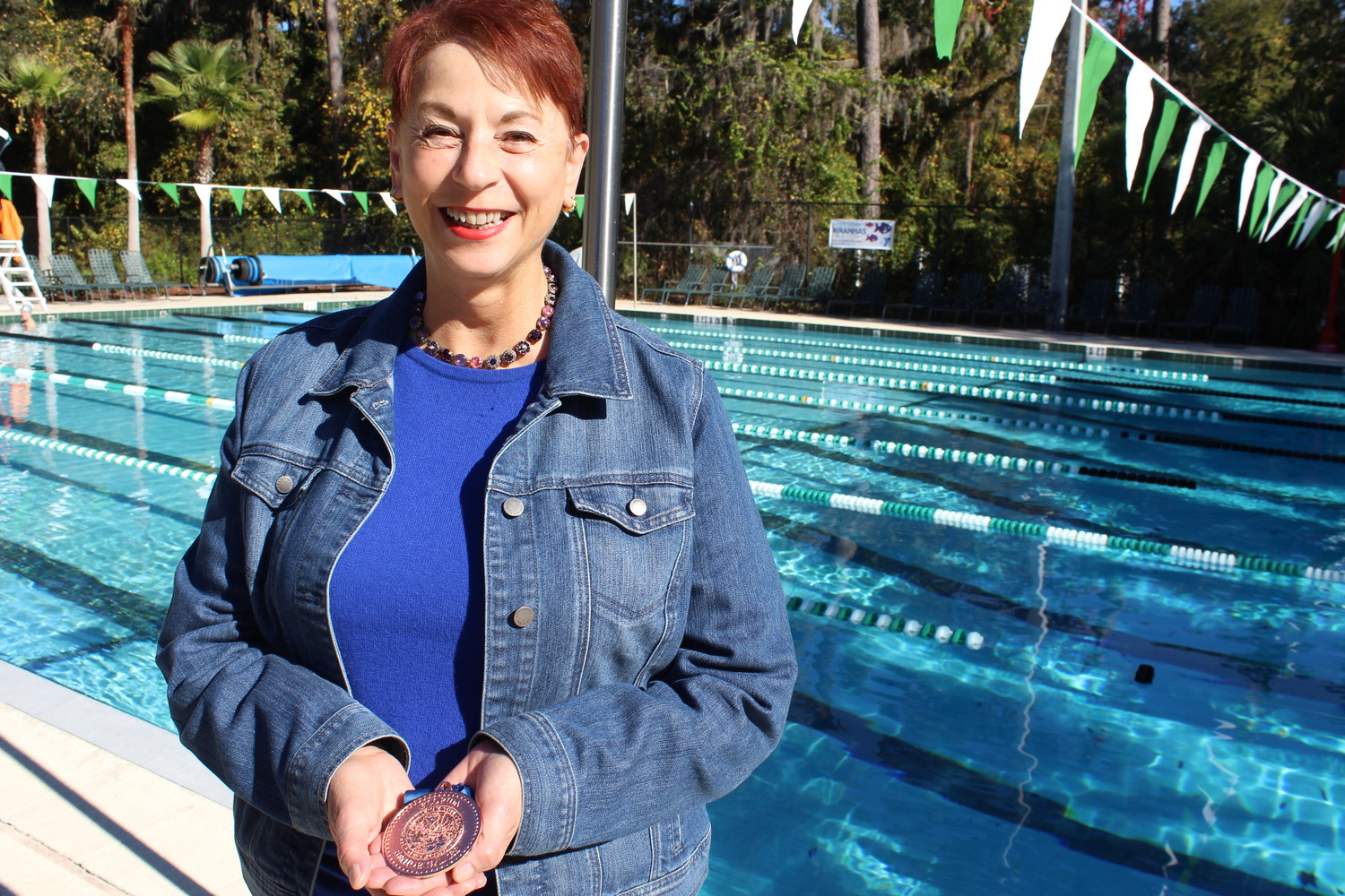 Dr. Rebecca Ann Miles stands by the Ponte Vedra YMCA pool where she trained to win a bronze medal in the 500-yard freestyle race of the Senior Olympic Games in early December. Miles dedicated her accomplishment to Dr. Jerry Rabinowitz, her primary care physician of 30 years in Pittsburgh who was killed in the Tree of Life Synagogue mass shooting in October.