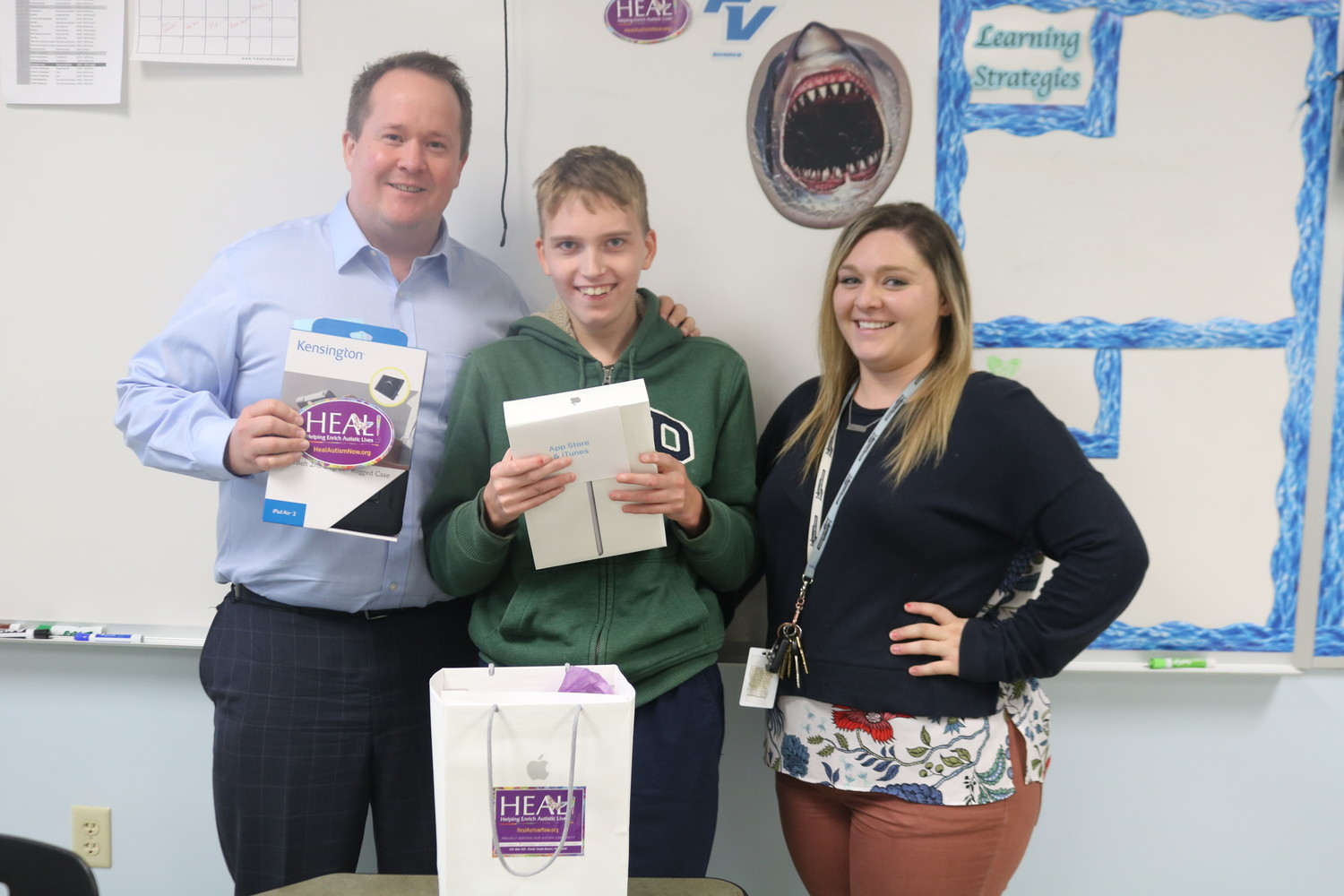 HEAL Foundation Executive Director Jason Gurka presents Ponte Vedra High School teacher Kaitlyn Goyette and student Owen Gee with an iPad, case and $25 iTunes gift card. The presentation was part of the nonprofit's iPads Helping Enrich Autistic Lives (iHEAL) initiative, which has gifted 400 iPads to local schools over the last four years.