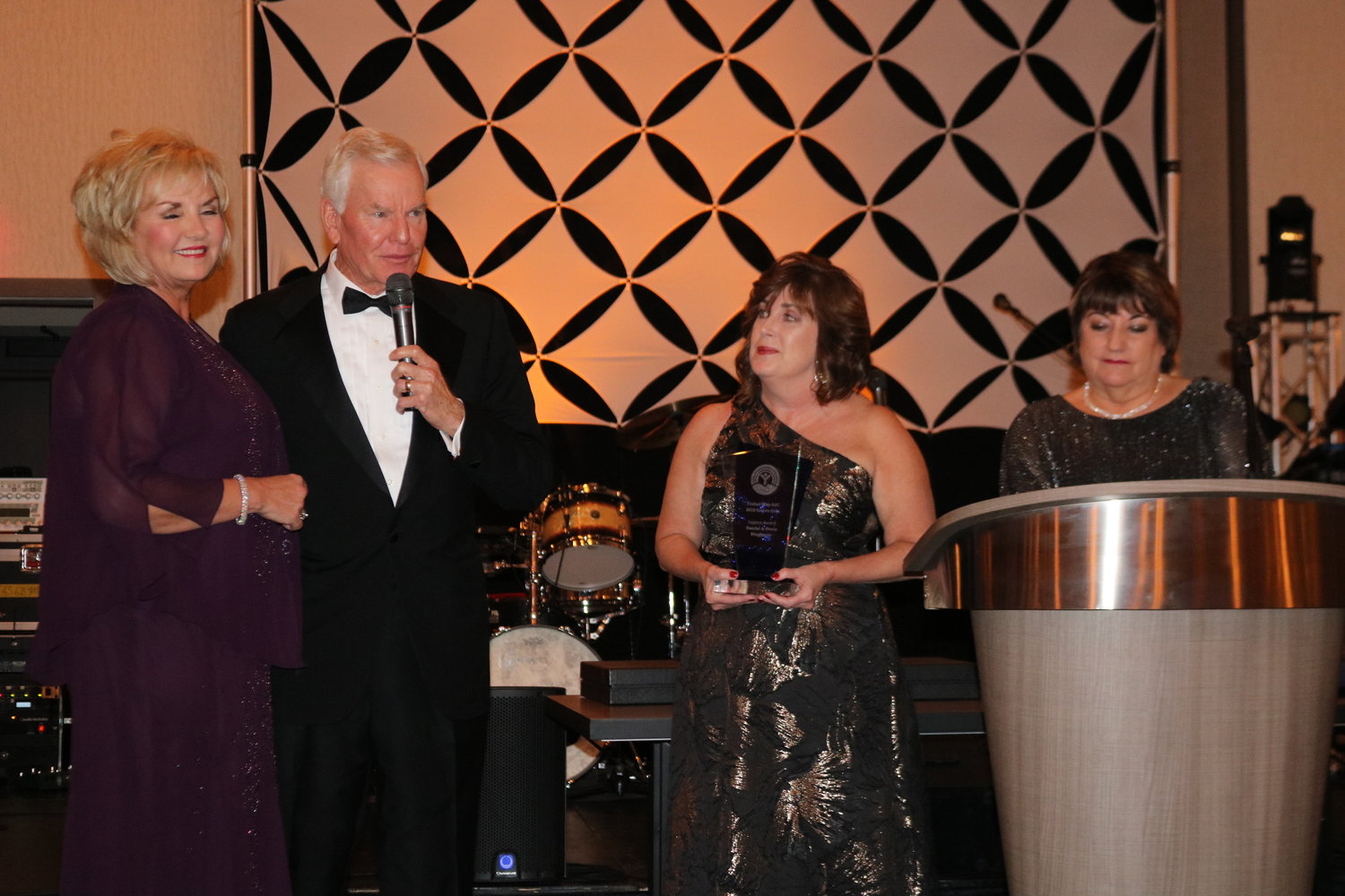 Paula and Randall Ringhaver, alongside Melissa Nelson and Bev Slough, address the crowd after receiving the Legacy Award.