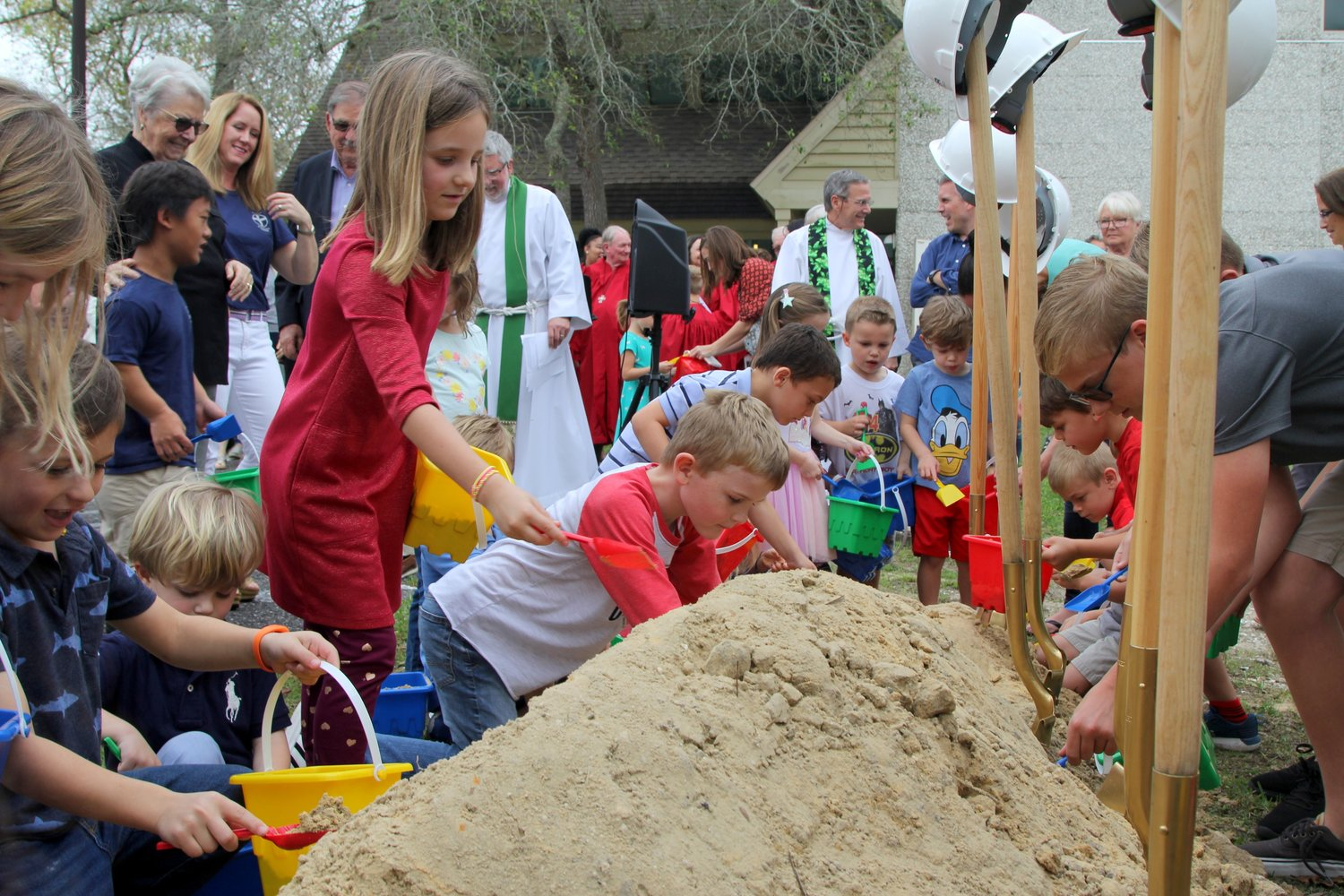 Children participate in the groundbreaking event for the church's new youth building.