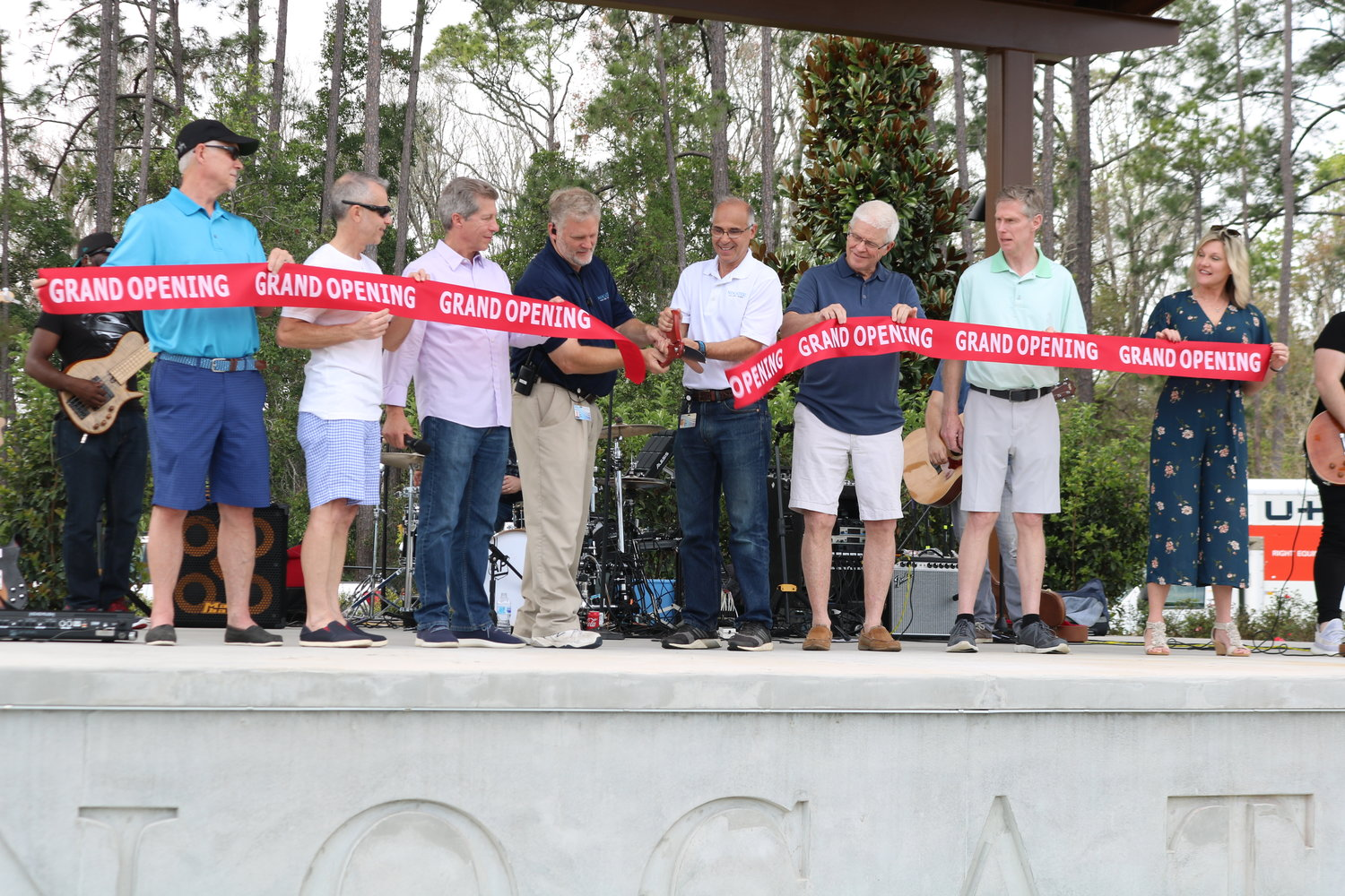 Representatives of the PARC Group and the Tolomato Community Development District participate in a ribbon-cutting ceremony to celebrate the grand opening of the Spray Water Park.