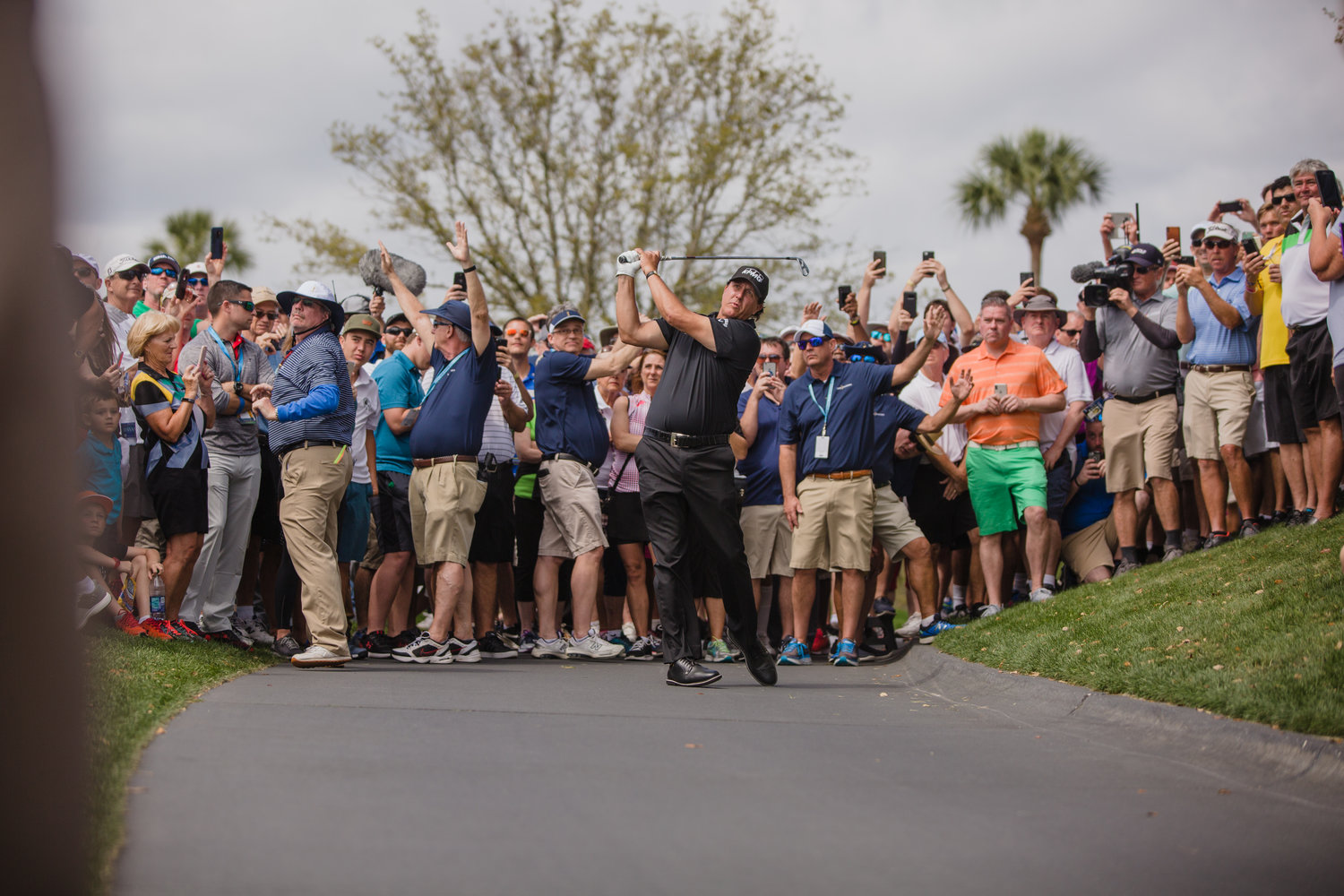 Phil Mickelson hits a shot from the cart path at THE PLAYERS. He's 2-over par after the first round.