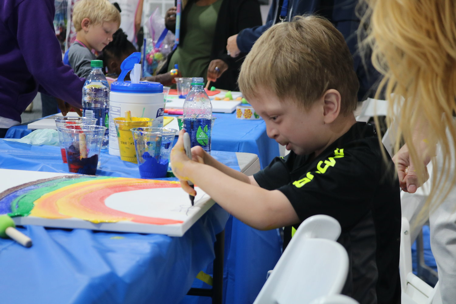 A kid at the event enjoys painting at an arts and crafts station.
