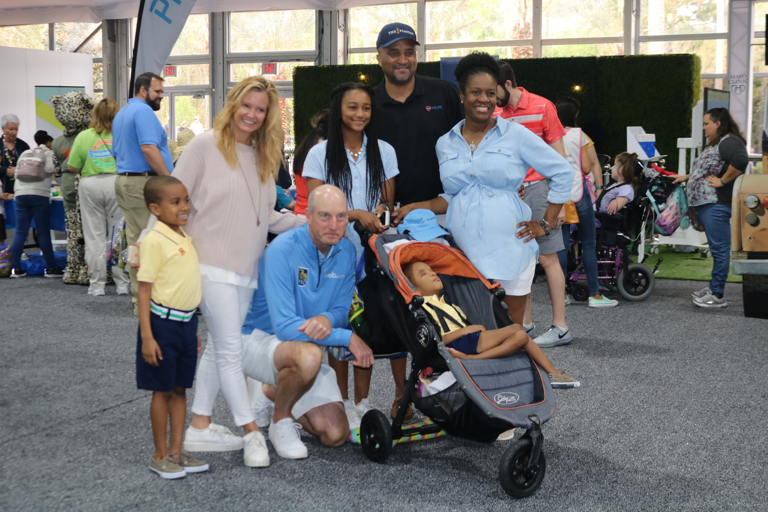"Tabitha and Jim Furyk gather with a family at ""These Kids Can Safari"" at THE PLAYERS on March 12."