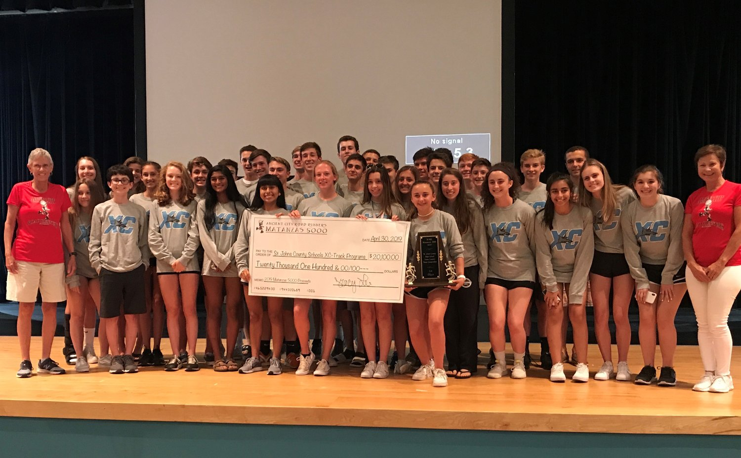 The Matanzas 5000 team presents a check for $20,100 to St. Johns County high school and middle school cross country and track programs.