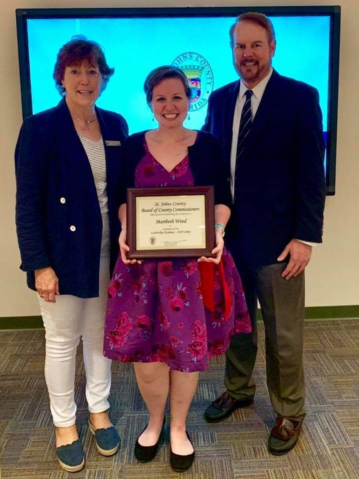Ponte Vedra Beach Branch Library Reference Librarian Maribeth Wood (center) receives a plaque recognizing her recent graduation from the St. Johns County Leadership Academy. Pictured alongside her is County Administrator Michael Wanchick and (insert name here). Wood also was recognized May 1 at the Library System's Staff Development Day.