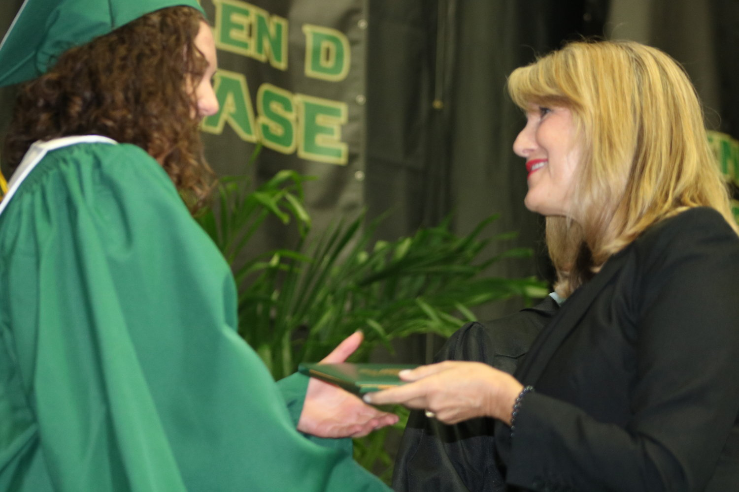 St. Johns County School Board Chair and District 4 Representative Kelly Barrera presents a Nease graduate with her diploma.