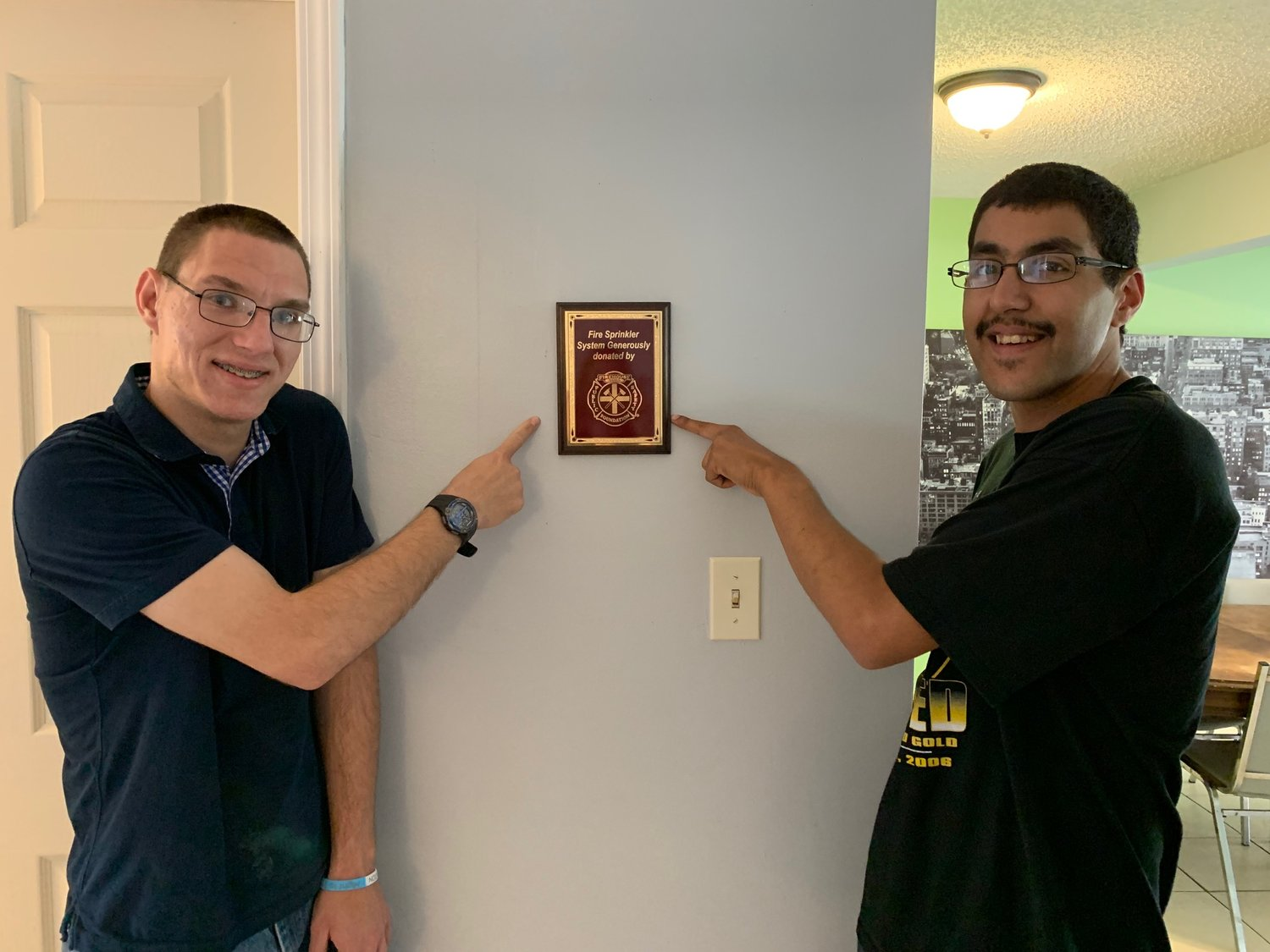 Residents of Angelwood pose with a plaque lauding a donation from the Firehouse Subs Public Safety Foundation to install an automatic fire sprinkler system at the nonprofit's residential group home.