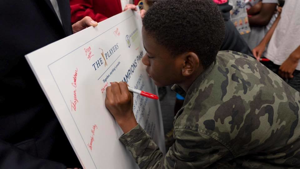 "Darnell, a middle school student, signed the CHAMPION's pledge at the event and will have the opportunity to earn a $1,000 ""Driven to Succeed"" scholarship."
