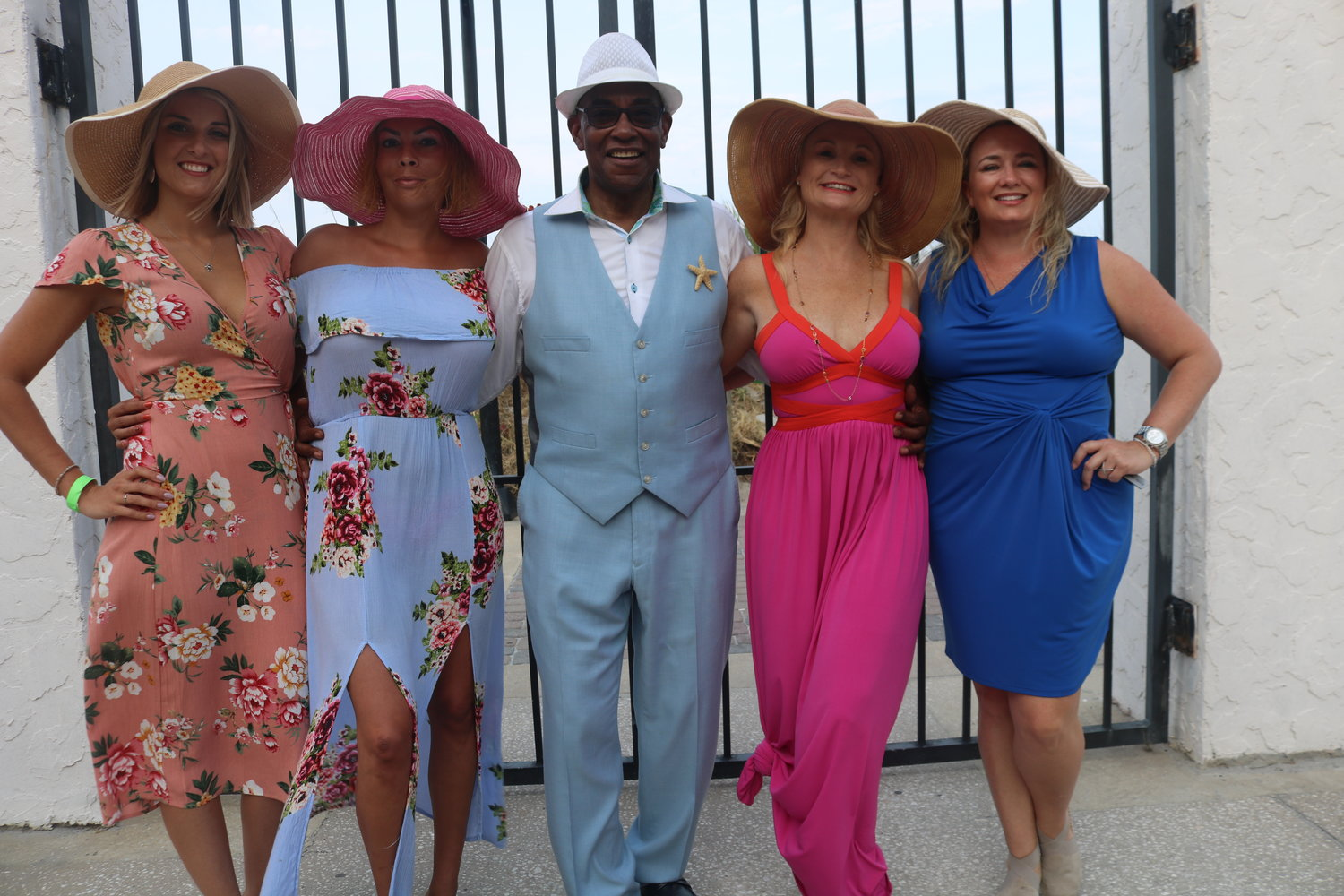 (left to right) Alyssa Sharpe, Dr. Crystal Makowski, Chelle Thomas and Trudy Toche pose with maître d', Sterling Joyce (middle) in their sundresses and hats at the Summer Pier Dance.