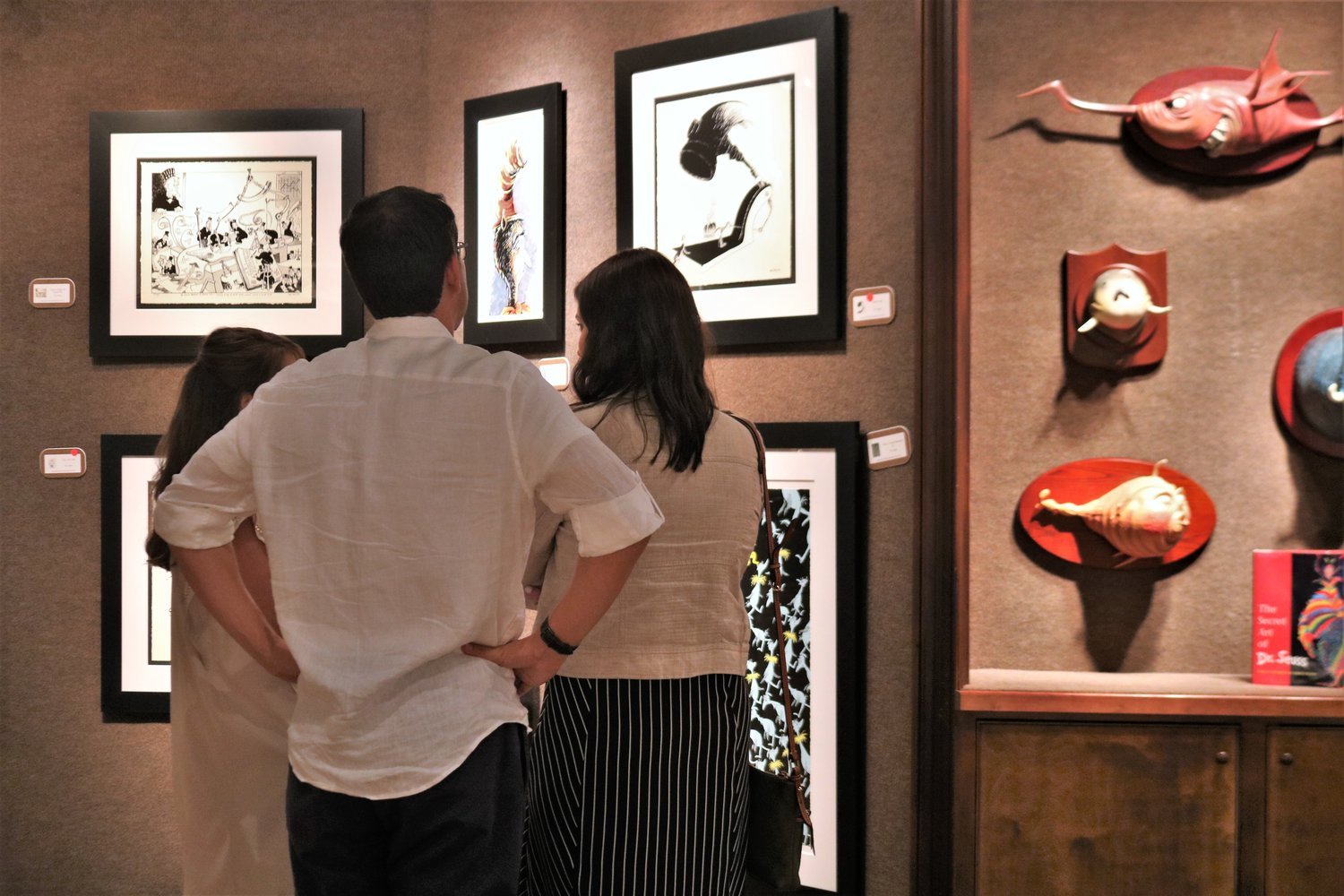 Exhibit opening attendees examine some of Dr. Seuss's political cartoons.