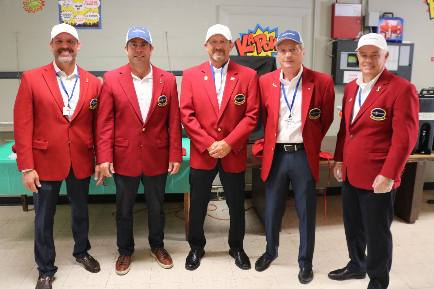 (Left to Right) The TPC Red Coats, (Adam Campbell, Kevin English, Jack Garnett, Lynn Stoner and Damon Olinto) serve some pizza and fun at Camp I Am Special on July 29.