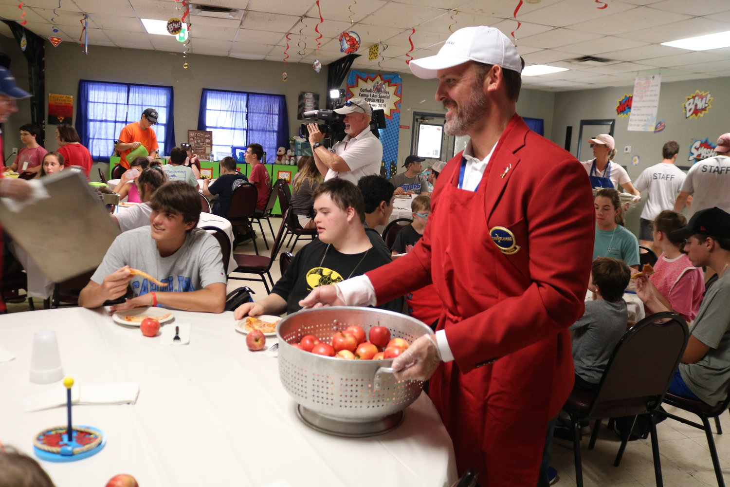 Newly selected Red Coat, 2019 chairman, Adam Campbell, offers campers apples for a healthy side.