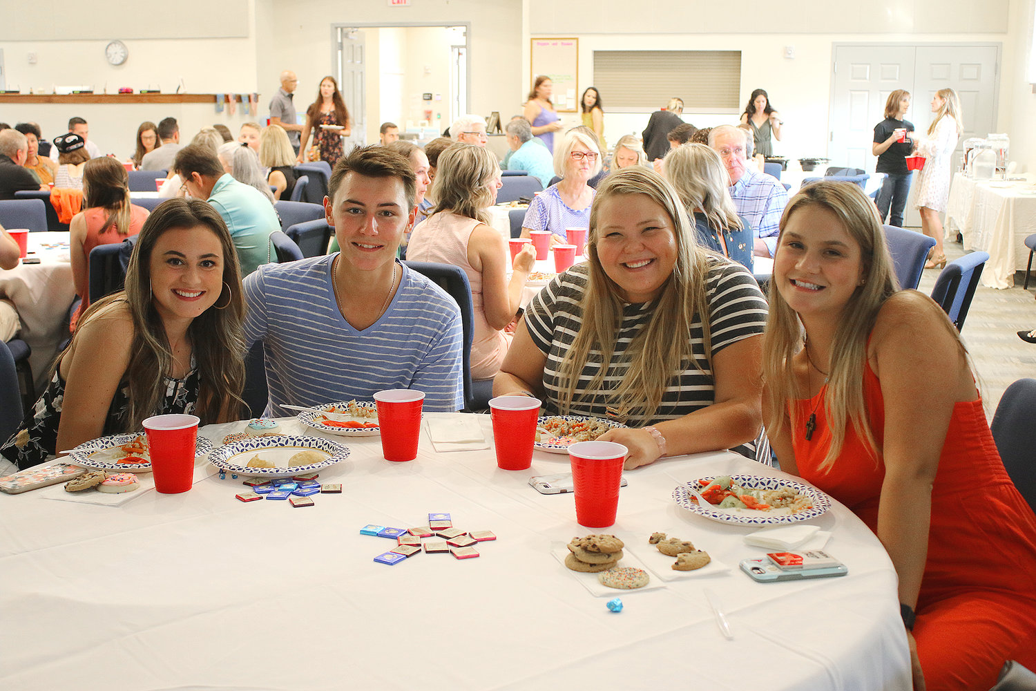 From left, Avery Middleton, Danny White, Katie Mahnken and Sofija Djukiz share a meal of traditional Kazakhstan food prepared by the eight young women who spent the summer working in the United States.