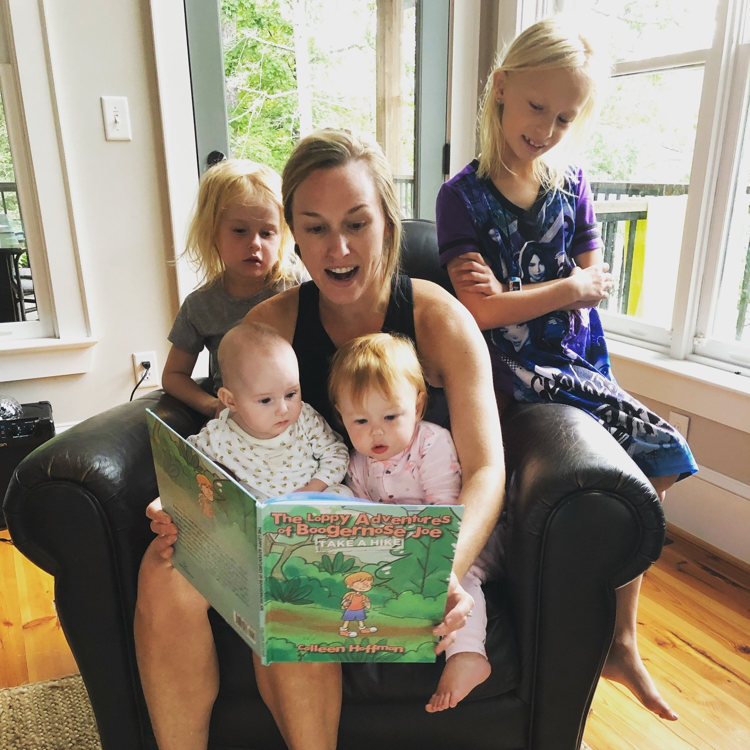 Colleen Hoffman, center, reads to toddlers Charlie Hughes (left) and Claire Hoffman (right) while the older girls, Margaret Hoffman (left) and Caroline Green (right) look on.