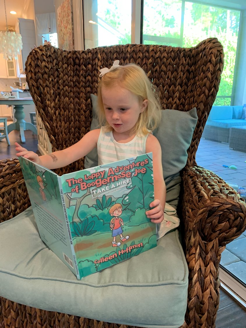 "Author Colleen Hoffman's daughter, Margaret, sits in a big, comfy chair to enjoy ""Take A Hike."""