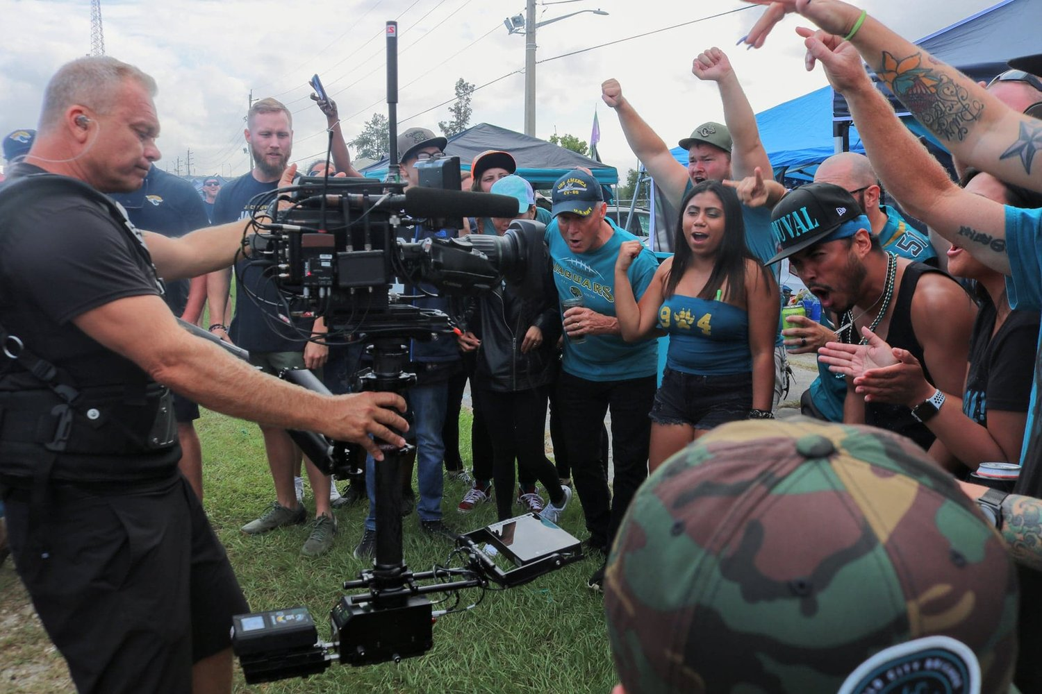 A cameraman from the NFL Network films Jacksonville Jaguars fans as they cheer for their team.
