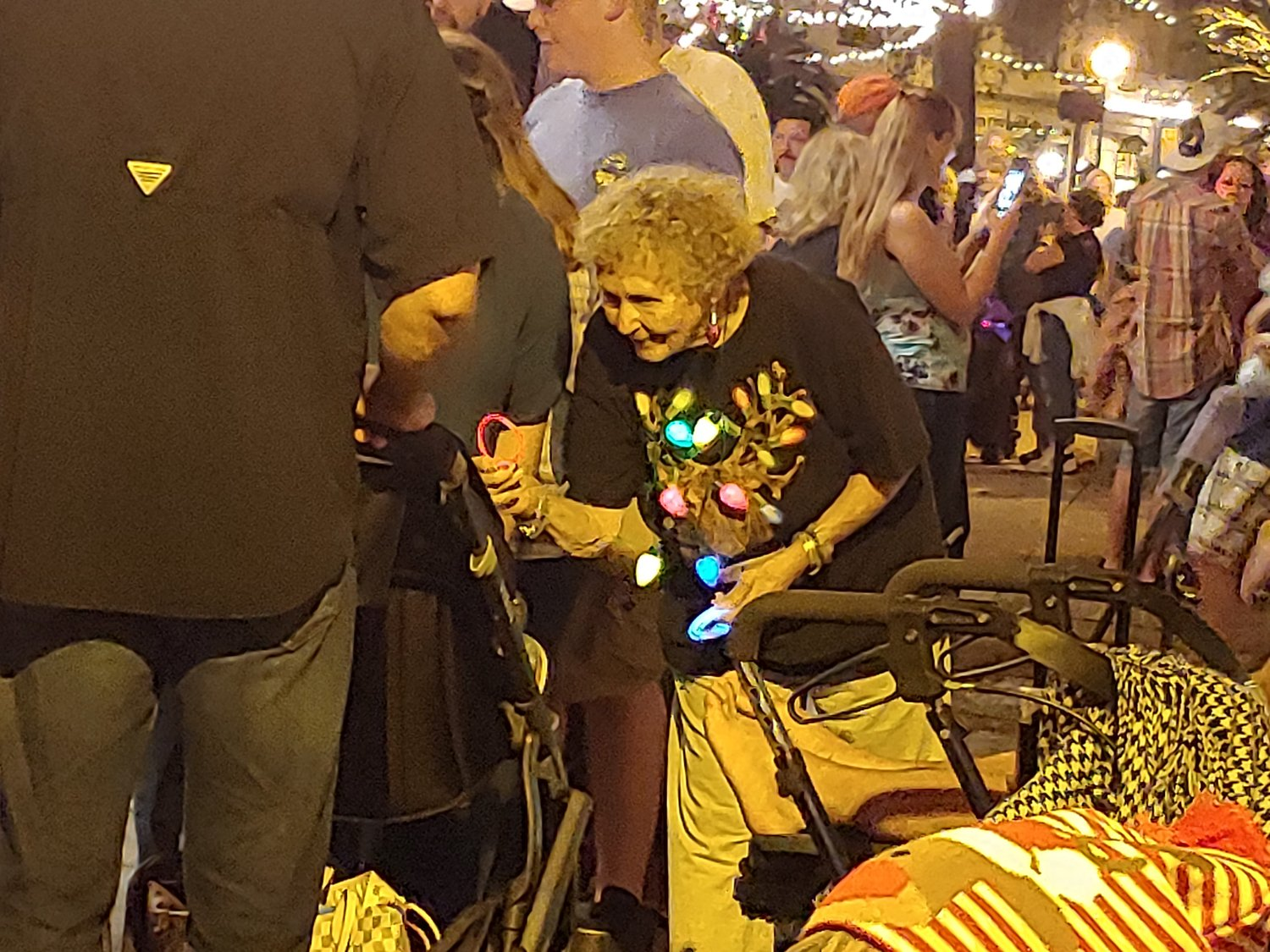 A woman hands out light-up toy jewelry to children as they walk through the plaza.