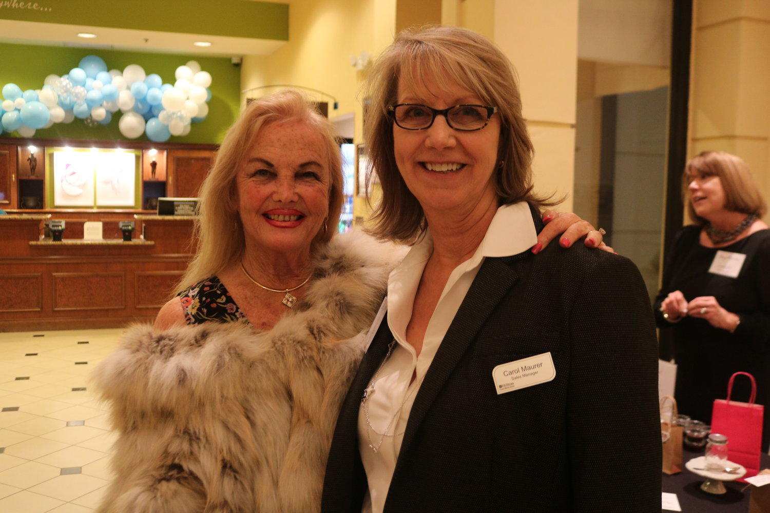 1.	Leigh Cort and Carol Maurer pose at the Hilton Garden Inn lobby, Nov. 18, for the Women's Food Alliance monthly event, hosted by Maurer, herself, and her catering company, Sawgrass Events.