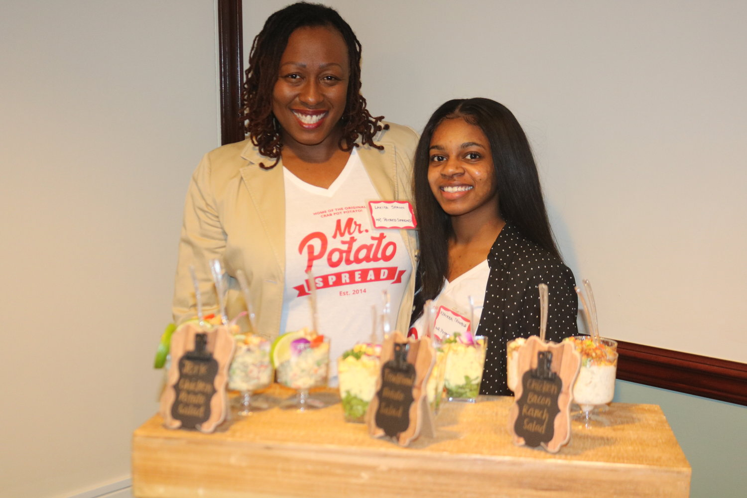 4.	Lakita Spann poses with coworker, Keairra Trimble, showing off the variety of potato creations of her business, Mr. Potato Spread.