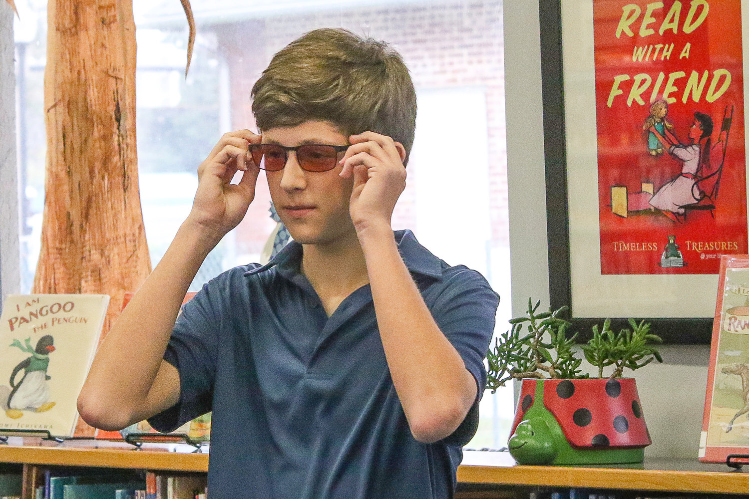 Drew Howell, a sophomore at Allen D. Nease High School, tries on glasses that allow him to see color indoors for the first time.