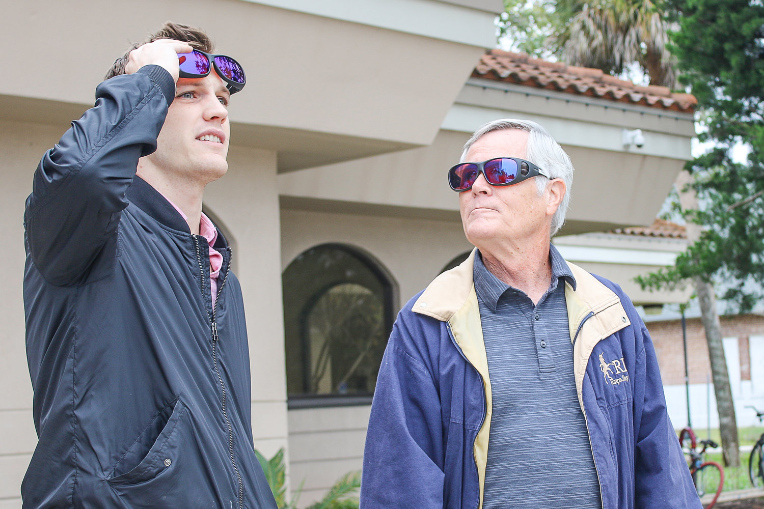 Mike McNabb, right, watches his son Jeff compare colors outside with and without EnChroma receptor sunglasses.