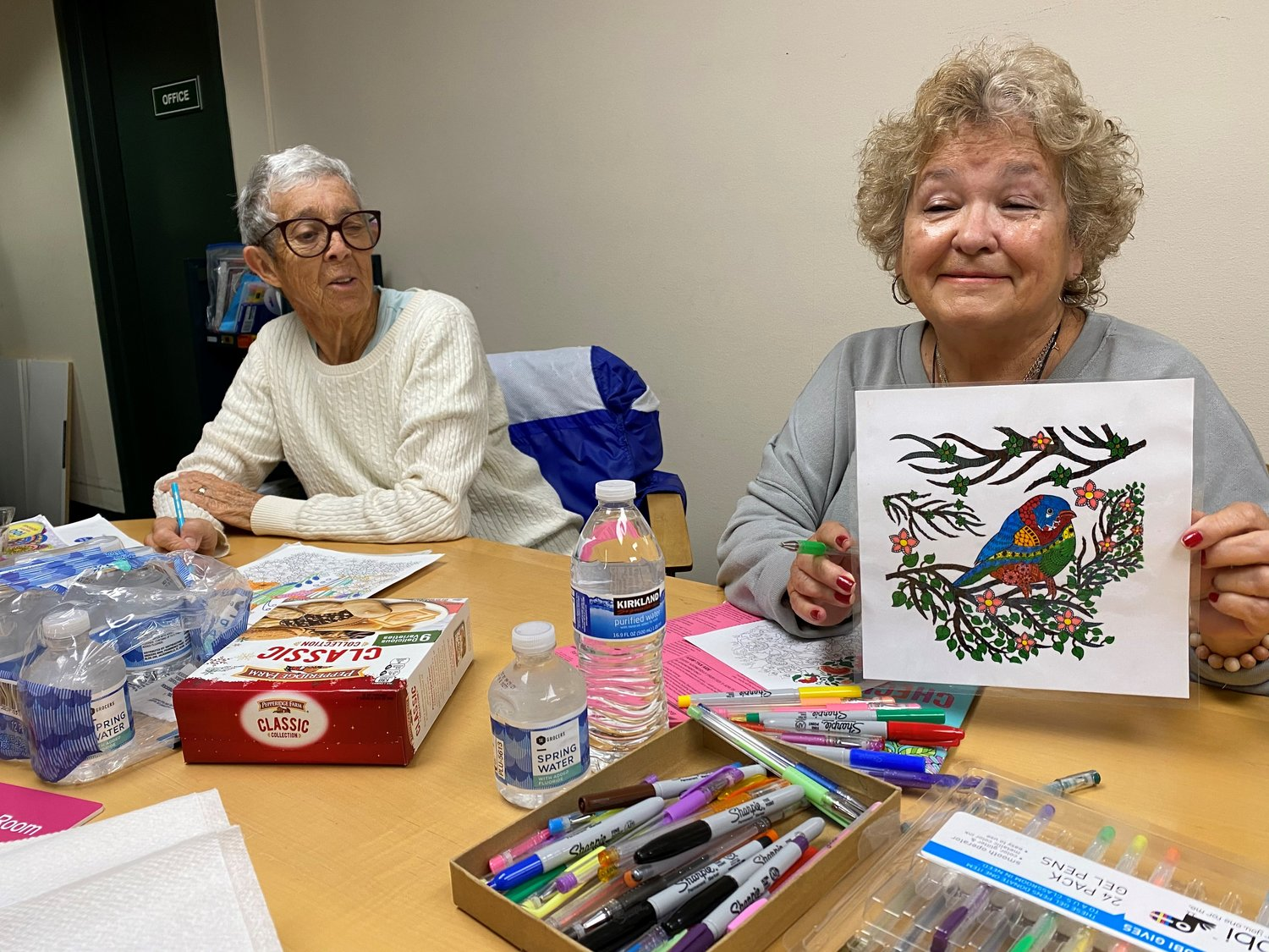 Gloria Montesino (right) holds up a picture she has finished as Phyllis Gallagher looks on.