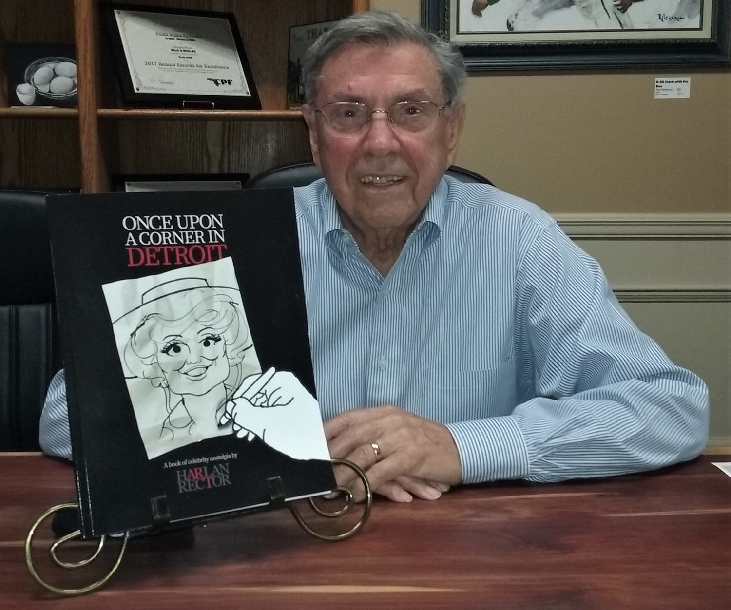 Harlan Rector shows off his book of celebrity caricatures.