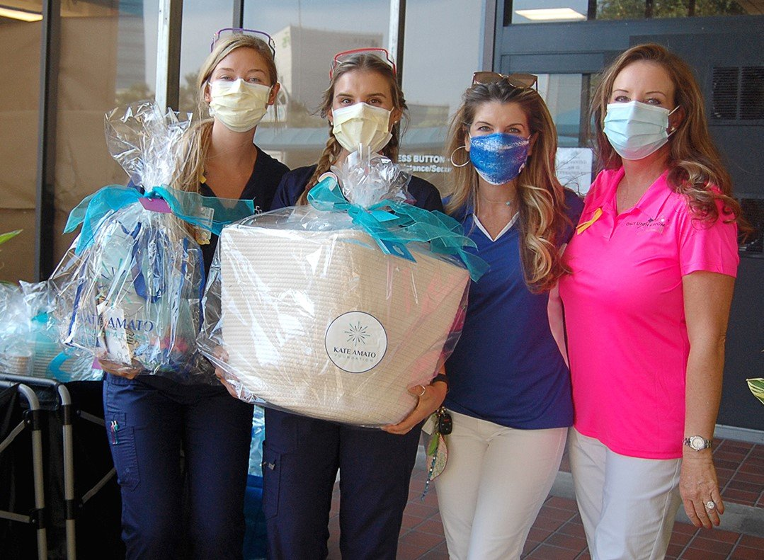 Wolfson Child Life specialists, left, receive Kate's Kindness Project baskets from Lisa Amato (Kate Amato Foundation) and Tina Toomey (Once Upon a Room).