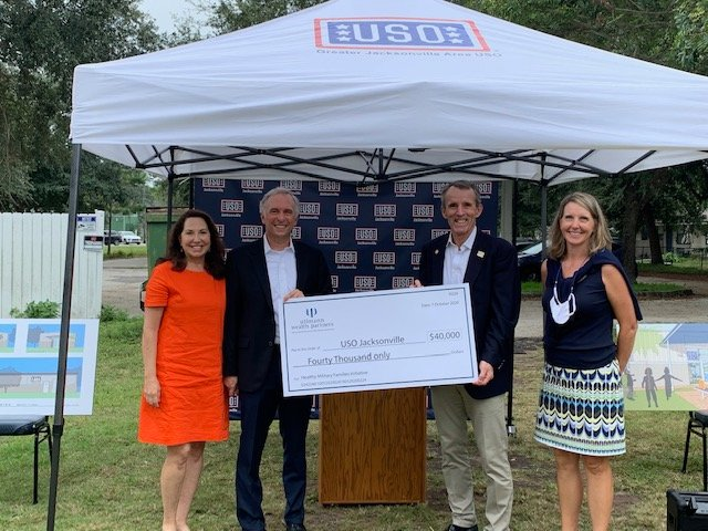 Glenn and Lisa Ullmann, left, present a check for $40,000 to USO of Greater Jacksonville Executive Director Michael O'Brien. At right is Francie Peters, marketing and communications manager for Ullmann Wealth Partners.