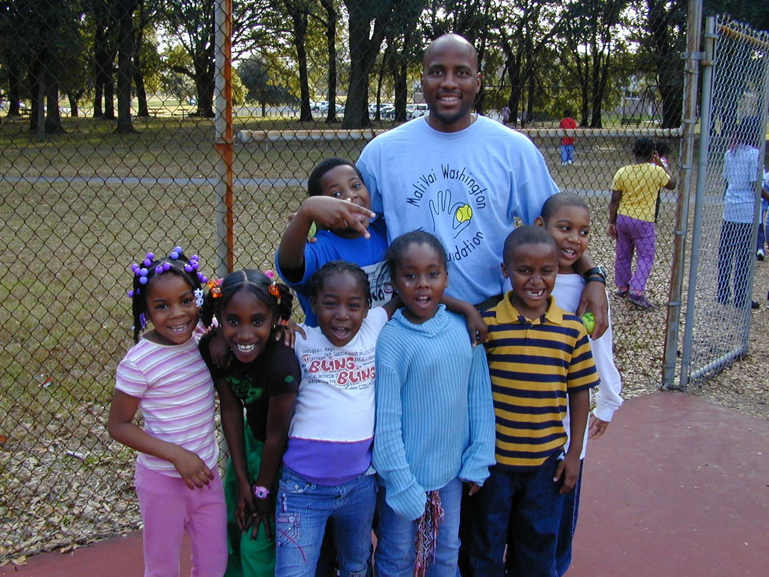 Mal Washington teaches tennis to MWYF students in 2004.