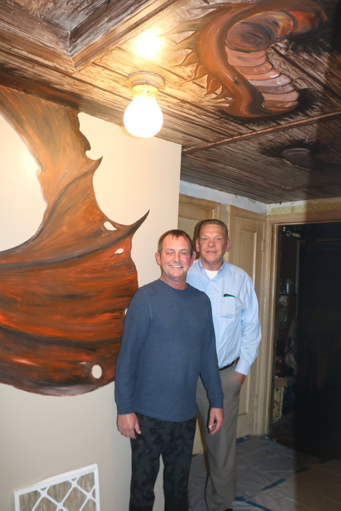 Hugh Tibbitts (left) and Tom Bright stand in front of their dragon hallway mural painted by Jerrod Brown.