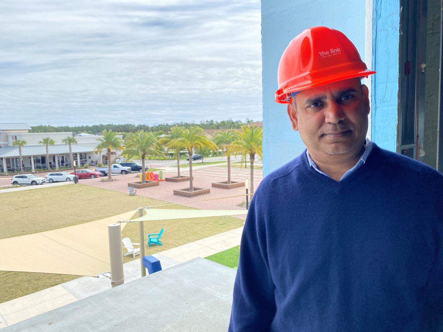 Raghu Misra, the man behind Wired2Perform and the link, stands on the second floor of the latter's building, which is under construction. When the facility is completed, large windows here will look out on a balcony.