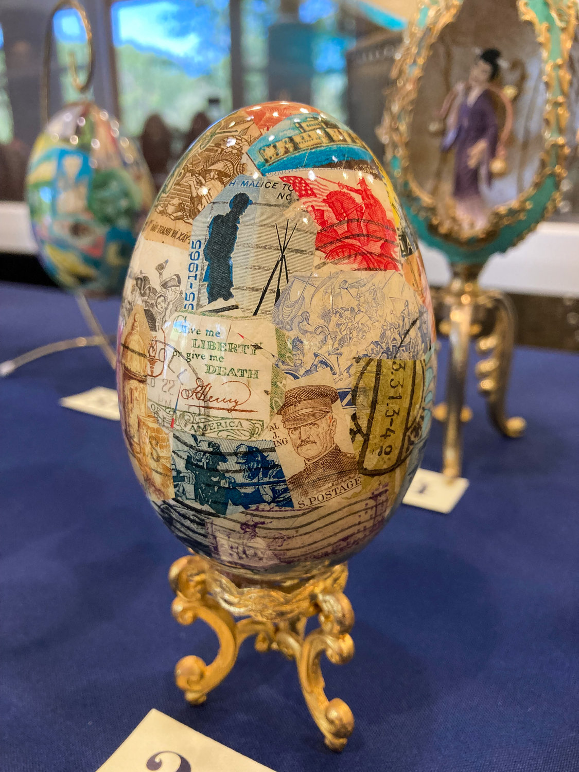 A goose egg decorated with collected stamps from around the world.