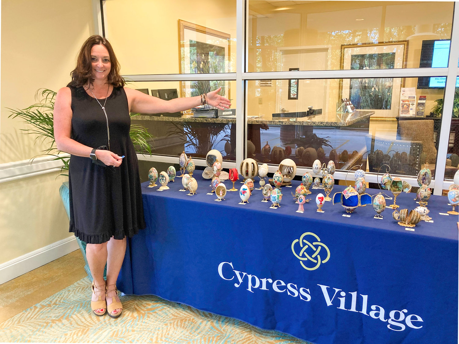 Lisa Green, director of sales and marketing for Cypress Village, stands in front of eggs hand-decorated by former Cypress Village resident Pat Kilpatrick. The eggs were auctioned off to help raise money for the facility's employee scholarship fund.