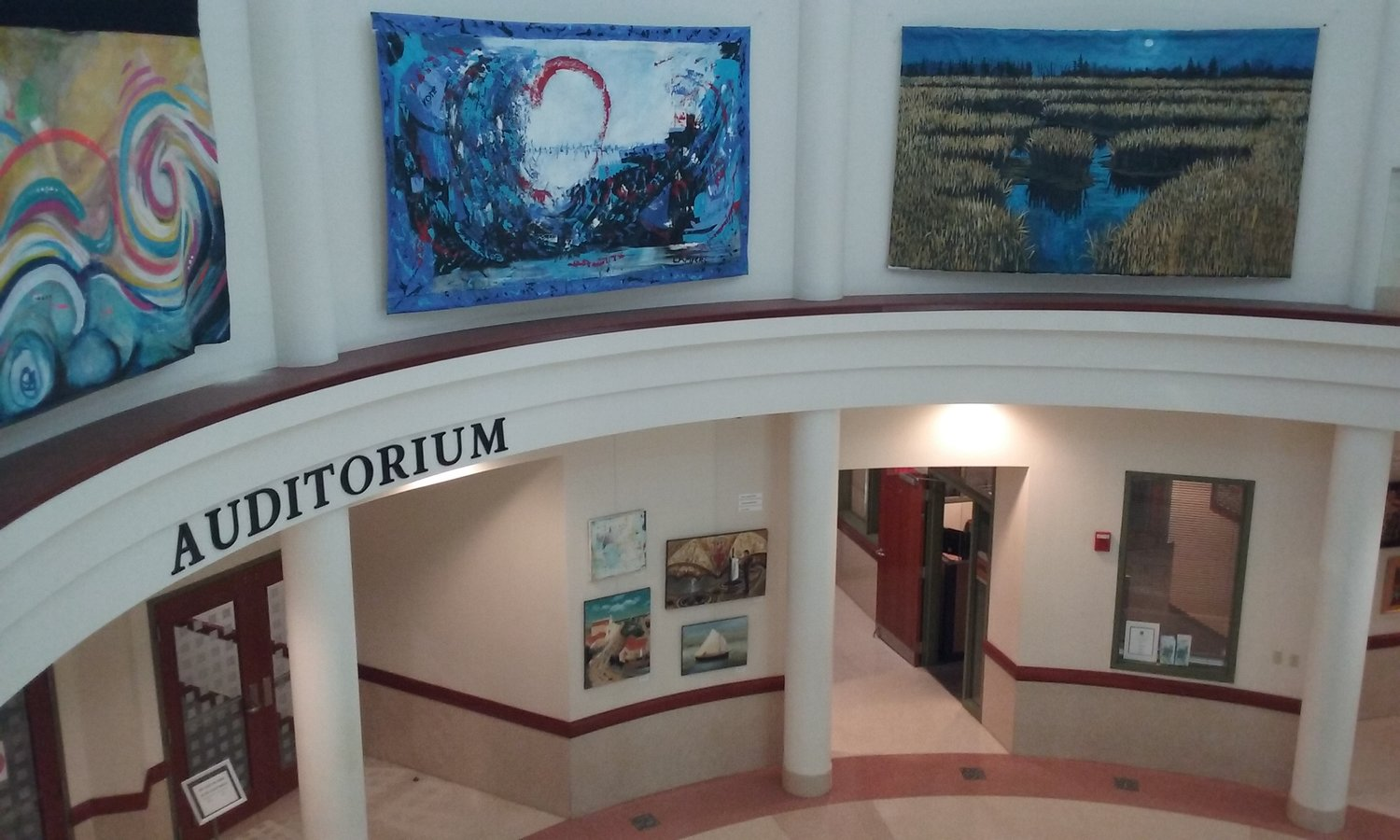 "Large paintings hang around the top portion on the rotunda. From left are ""Early Marley Morning"" by Don Kight, ""Emergence"" by Lisa Myers and ""Full Moon Marsh"" by Ken Vallario. Not pictured: ""Matanzas"" by Patrick Madden."