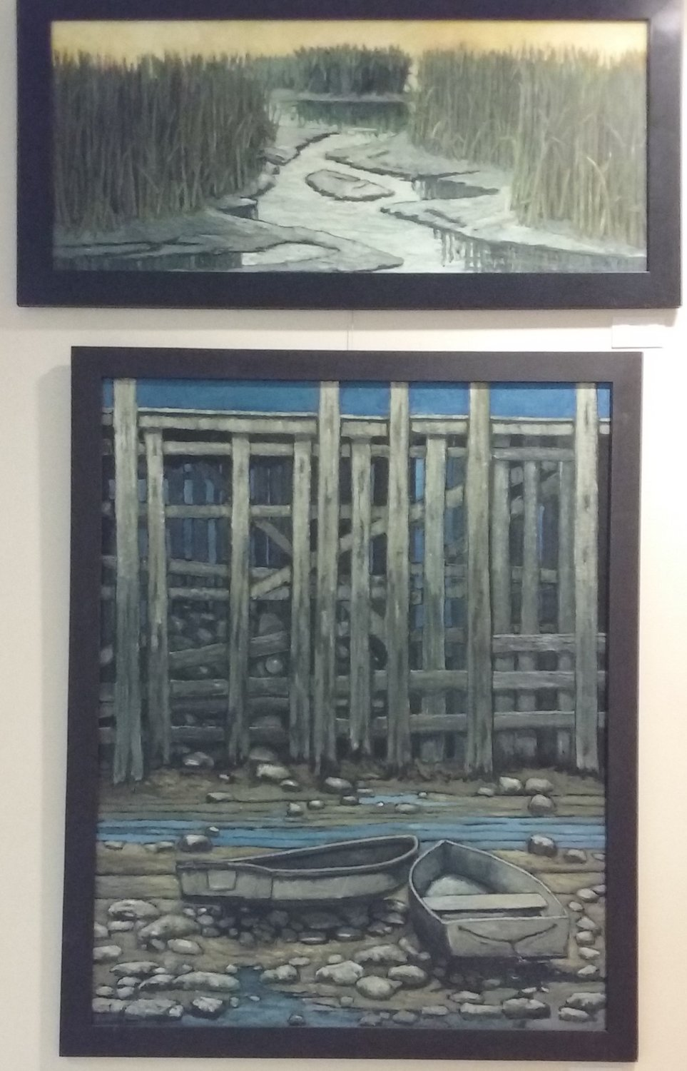 "Two paintings by Ken Vallario hang on one wall of the rotunda. The top one is ""Golden Marsh"" and the one below it is ""Under The Boardwalk."""
