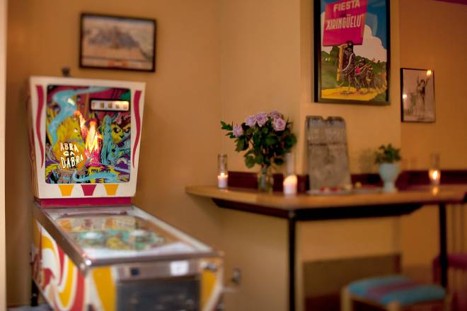 The dining room has an open floor plan with counters for dining and a pinball machine